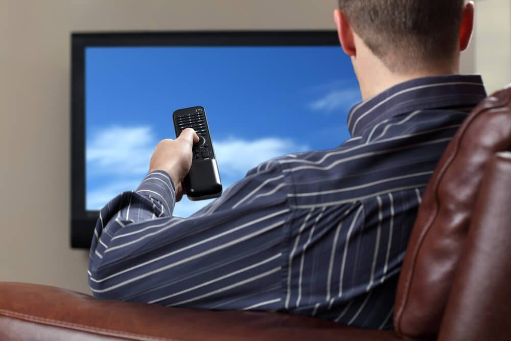 Guy watching cable television