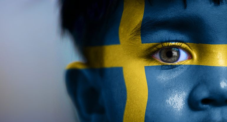 young boy with a Swedish flag painted on his face